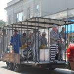 Guys in prison suits on parade float in jail